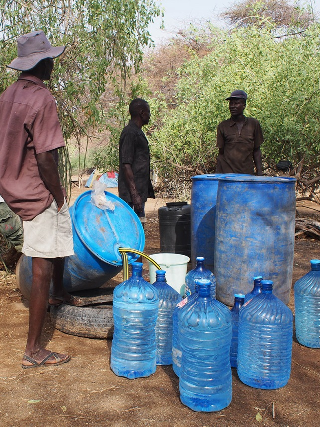 Benjamin, Ektala and William with all the blue barrels used to purify and store drinking water