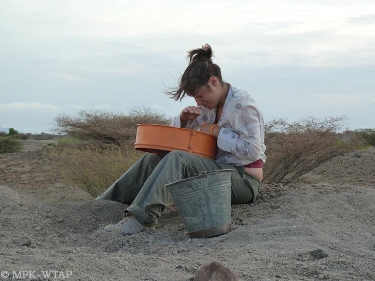 Student excavator Sol Galan sieving