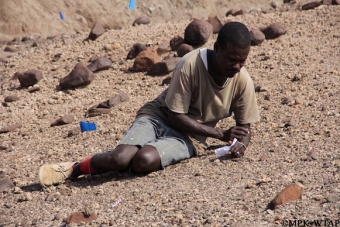 2012_Sammy inspecting a stone tool
