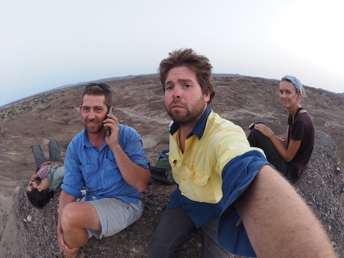 Nicholas, Jason and students Evan and Jenna climb a hill to get phone network